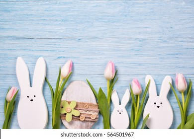 Easter background with white rabbits, pink tulips and easter egg, top view