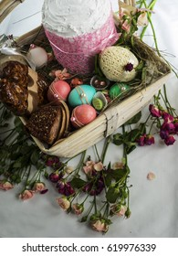 Easter basket for ceremony witn different food: Easter cake, colored eggs, jar with foie gras, sweets, homemade fried sausage, boiled pork, egg from white chocolate, laid on hay