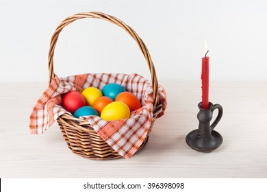 Easter basket with colored eggs candle in a candlestick