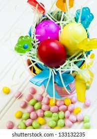 Easter basket with colorful eggs in grass.