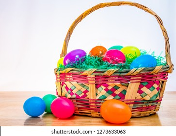 Easter basket with colorful plastic Easter eggs. Vintage woven wicker egg hunt basket, green grass, and vibrant colored classic eggs.