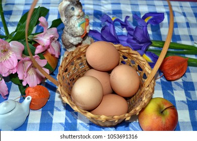 Easter basket with eggs, iris flowers, Peruvian lilies, cape gooseberries, teapot, apples  and Easter bunny on the blue-white checked tablecloth, Easter table decoration