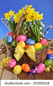 Easter basket with eggs and narcissus on old weathered wooden board