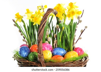 Easter basket with eggs and narcissus on white background