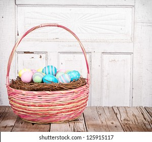 Easter basket with Easter eggs on a wooden plank with antique cracked panel for background