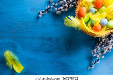 Easter Basket with easter eggs and yellow feathers and catkins on blue wooden background.