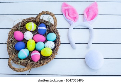 Easter basket full of colorful eggs and cute bunny ears.