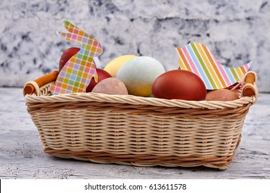 Easter basket with paper cutouts. Pile of dyed chicken eggs.
