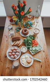 Easter beautiful wooden table with flowers, tulips, fresh vegetables and natural eggs. festive bright family Breakfast. joy, morning, home, coffee, eggs, dessert, sandwiches, bread.