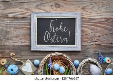 "Easter black board with Easter eggs, flowers and spring decorations on rustic wood. Text ""Frohe Ostern"" on the blackboard means ""Happy Easter"" in German."