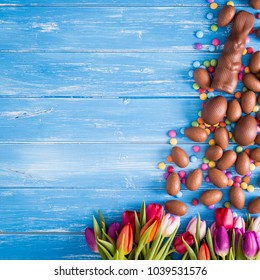 Easter blue background with chocolate rabbit, easter eggs and tulips