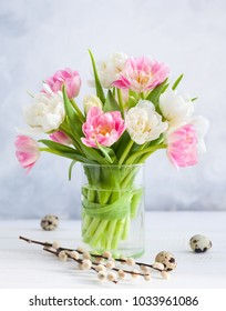 Easter bouquet of spring tulips and Easter decor on white wooden table. Easter concept with copy space.