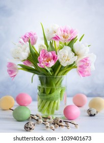 Easter bouquet of spring tulips and Easter eggs  on white wooden table. Easter concept with copy space.