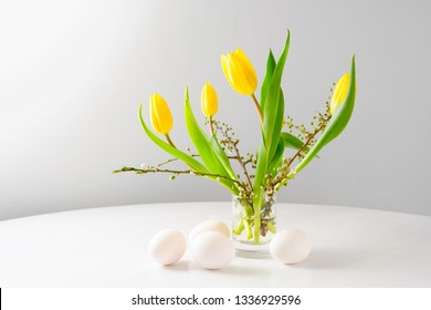 Easter bouquet with yellow tulips and spring branches in al glass an four eggs on a white table against a gray background with copy space, selected focus, narrow depth of field