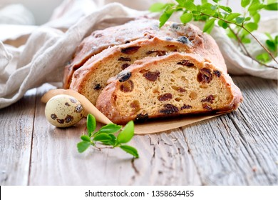 Easter Bread (Osterbrot in German). Close-up on traditional fruty bread on rustic wood with fresh leaves and quail eggs. Traditional German dessert for Easter celebration.