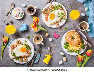 Easter breakfast flat lay with scrambled eggs bagels, orange tulips, bread toast with fried egg and green asparagus, colored quail eggs and spring holidays decorations. Top view.