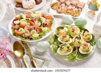 Easter breakfast with fresh salad with quail eggs, stuffed eggs with mayonnaise and rolled ham slices with salad on festive table