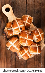 Easter Breakfast with Hot Cross Buns, served on Wooden Chopping Board, Dark wooden Rustic Background. Top View