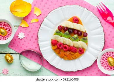 Easter breakfast idea - pancakes shaped colorful Easter egg with pieces of fruits and berries