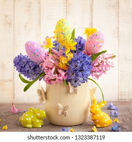 Easter breakfast table with tea,eggs in egg cups, spring flowers in vase and Easter decor.