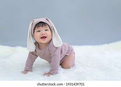 Easter bunny, Baby in rabbit cloth. Asian happy baby smiling, crawling on gray background. Cute 6 months baby crawling with copy space as Easter concept, baby or kid department in hospital