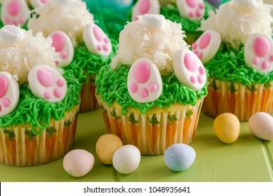 Easter bunny butt cupcakes made with lemon cake and filled with lemon curd with candy Easter eggs in foreground