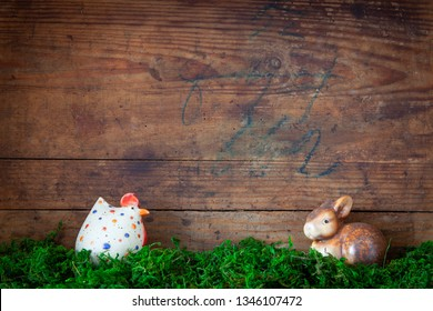 easter bunny and chicken on moss before old wooden background