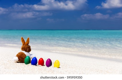 Easter bunny with colorful easter eggs in a row on a tropical beach