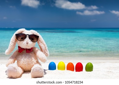 Easter bunny with colourful easter eggs on a tropical beach