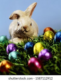 Easter bunny decoration and chocolate eggs on grass