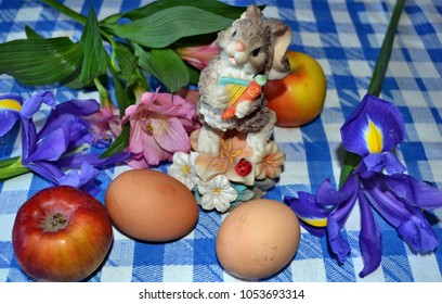Easter bunny with  Easter eggs, iris flowers, Peruvian lilies and apples on the blue-white checked tablecloth, Easter decoration