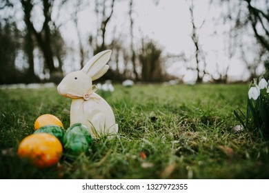 Easter bunny and eggs on a green grass, snowdrops on the background
