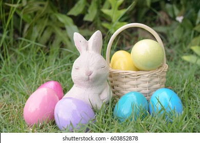 Easter bunny and Easter eggs, rabbit statues and colorful pastel eggs at the backyard garden. Soft focus on the eyes of Easter bunny. Easter eggs hunting activity concept.