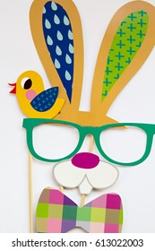 An Easter bunny face with glasses and bow tie made from photo booth props on a white ground