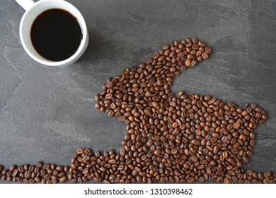 An Easter bunny made of freshly roasted coffee beans laid out with a cup of coffee - concept for fresh coffee enjoyment on easter and as easter gift in the form of coffee beans