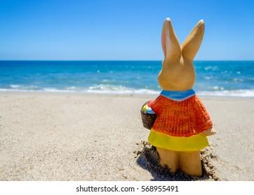 Easter bunny on the sandy beach near the ocean