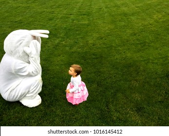Easter bunny playing peep-bo with a little toddler while egg hunt