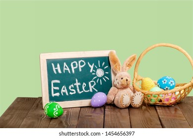 Easter bunny rabbit with green painted egg on green background. Easter holiday concept.          - Image