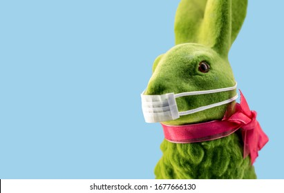 Easter bunny or rabbit with a medical mouth mask to prevent corona virus. Concept of cancellation of easter or other seasonal holidays during pandemic.