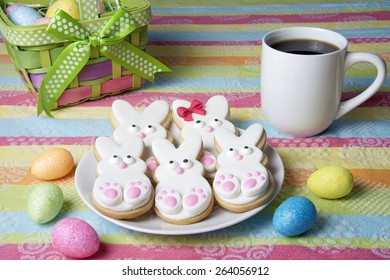 Easter Bunny Sugar Cookies homemade covered in home made marshmallow fondant, decorated with candy eyes, nose, feet and bow. Large and small bunnies. On a plate with cup of coffee colorful table cloth