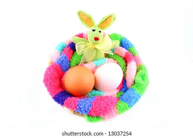easter bunny and two eggs in a fluffy multicolored clutch