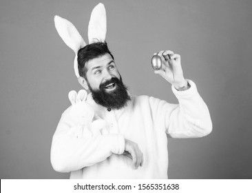 Easter bunny. White bunny symbol of easter. Guy with toy and easter egg on violet background. Enjoy tenderness. Spring holiday. Easter when you are parent. Man handsome face wear white bunny ears.