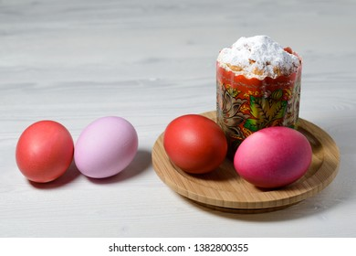 Easter cake and boiled painted eggs on a wooden plate