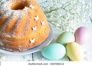 Easter cake with candy butterflies and eggs on floral spring abstract white background