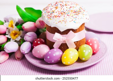 Easter cake and colorful polka dot eggs on the plate and flowers on the foreground