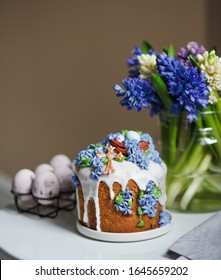 Easter cake with cream, decorated with nuts and berries, flowers, stands on a stand. lifestyle