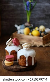 Easter cake decorated with white glaze and macarons. Side view, wooden background, spring composition, flowers, Easter eggs.