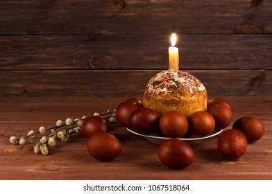 Easter cake, Easter eggs and a lighted candle on a wooden table