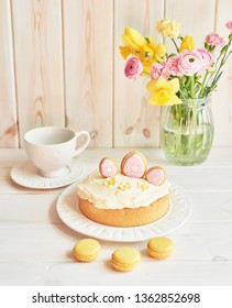 Easter cake with gingerbread on the table, the table is decorated with flowers, macaroons  and eggs