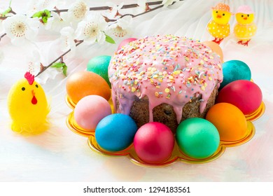 Easter cake with icing sugar, colorful painted eggs, bouquet of spring flowers and decorative chickens. Traditional Easter treats of Russia and Ukraine for Orthodox Easter. Easter symbols